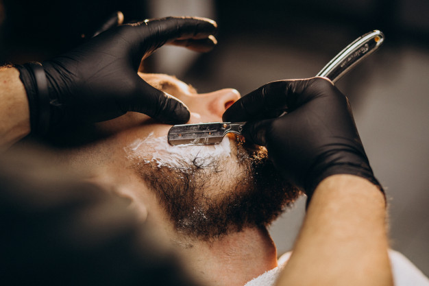 handsome-man-cutting-beard-barber-salon_1303-20972
